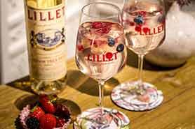 Lillet Gläser mit Lillet Wildberry Drink mit Himbeeren und Heidelbeeren vor Lillet Blanc Flasche und neben Schale mit Erbeeren und Brombeeren