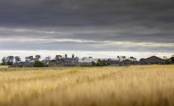 Getreidefelder vor einer Whisky Destillerie